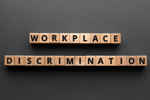 Workplace discrimination - words from wooden blocks with letters, employment discrimination legislation and issues concept, top view gray background